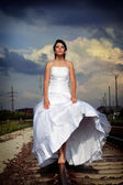 Beautiful young brunette bride is walking on the railway — 图库照片