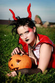 Beautiful gothic female holding a halloween pumpkin — Stock Photo