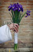 Bride is holding her wedding iris bouquet on a old castle wall background — Stock Photo