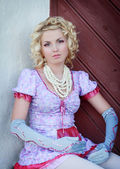 Beautiful blond curly girl is acting like a pretty porcelain doll — Stock Photo