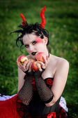 Beautiful gothic female holding apples in her hands — Stock Photo