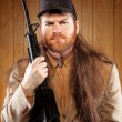 Southern Hick with a rifle and flowing hair - Stock Photo