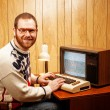 Handsome Nerdy Adult using a Vintage Computer TV - Foto Stock