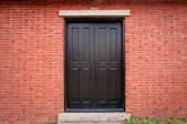 Black Door on Brick Exterior — Stock Photo