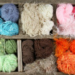 Many colorful yarns in wooden box — Stock Photo
