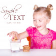 Cute little girl dunking cookie in milk — Stock Photo #10447278
