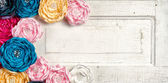 Multi colored vintage flowers on aged door — Stock fotografie