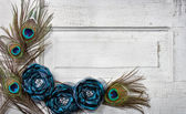 Peacock feathers and flowers on vintage door — Stock Photo