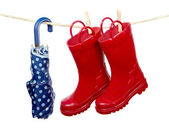 Rain boots and umbrella on a clothes line — Stock Photo