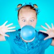 A silly girl dressed in blue blowing a blue bubble — Stock Photo