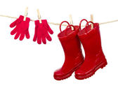 Red Boots and Red Gloves on a clothes line — Stock Photo