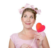 A silly woman looking up holding a red heart — Stock Photo