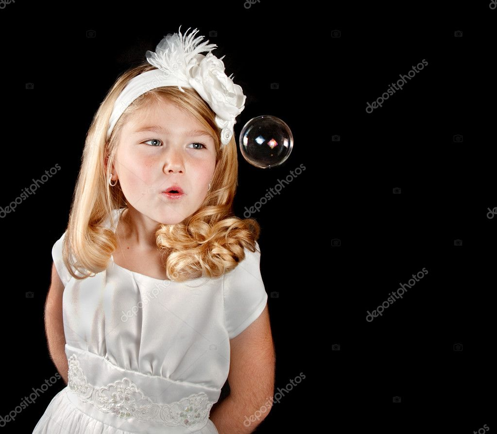 A cute girl dressed in white blowing a clear bubble, on a black background. — Stock Photo #8654333