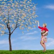 A woman reaching up picking money off a tree — Stock Photo #8853260