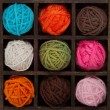 Nine colorful balls of yarn in printers box — Stock Photo