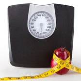 Close up of a scale and an apple/pear with a measuring tape — 图库照片