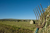 A pitchfork stuck in a bale of hay with a farm landscape in the — Stock Photo