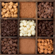 Assorted chocolate chips in a printers box — Stock Photo