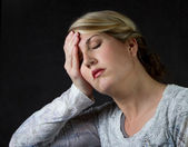 A woman upset or with a headache — Stock Photo