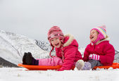 Two laughing kids sledding — Stock Photo