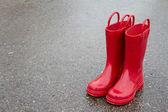 красный дождь сапоги на мокрой мостовой — Стоковое фото