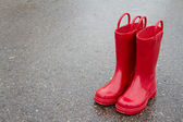 Red rain boots on wet pavement — Stok fotoğraf