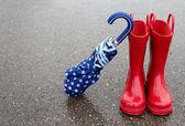 Red rain boots and umbrella — Stock Photo