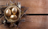 Three golden eggs in a nest — Stock Photo