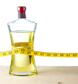 A measuring tape around a bottle of olive oil — Stock Photo