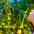 Brunette girl blowing soap bubbles in the wind - Stock Photo