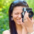 Young brunette girl trying to take pictures with old camera — Stock Photo