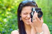 Jeune fille brune en train de prendre des photos avec le vieil appareil photo — Photo