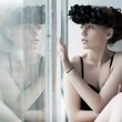 Melancholy - lovely girl sitting by the window — Stock Photo