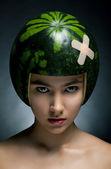 Schöne mode modell mit grüne frische melone als schutzhelm — Stockfoto