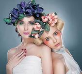 Two graceful women- lovely brunette and pretty blonde posing in studio — Stock Photo
