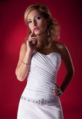 Fasion model blonde in wedding dress posing over red background — Stock Photo