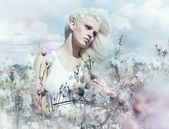 Spring landscape - attractive gentle blonde girl in flowering meadow — Stock Photo