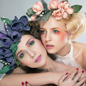 Two pretty girls blonde and brunette in colored wreaths hugging — Stock Photo