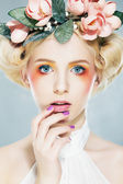 Beautiful blonde supermodel in wreath of flowers studio shot — Stock Photo