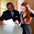 Negotiations between red-haired girl and black american man — Stock Photo