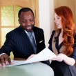 Stock Photo: Red hair young businesswoman and black american businessman in office space
