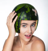 Fancy young happy girl with fresh green melon as a hard hat — Stock Photo