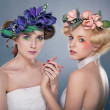 Two lovely nymphs - blonde and brunette in colorful wreath of flowers — Stock Photo