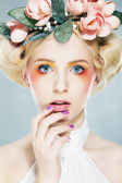 Lovely blonde super model in wreath of flowers and bright makeup — Stock Photo