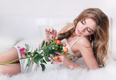 Lovely sexy girl lying in bed with branch of flower - fresh roses — Stock Photo