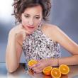 Lovely young girl with fresh halves of oranges sitting — Stock Photo