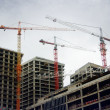 , three cranes on top of high-rise building — Stock Photo