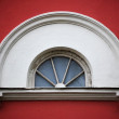 Arc attic vintage window on red stucco wall ; - Stock Photo