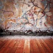 Dark brown room with peeled stucco wall and wooden floor — Stock Photo