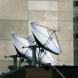 Two sattelite dishes on top of roof - Stock Photo